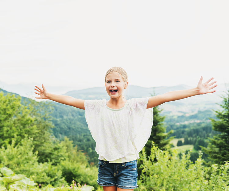 Little kid girl hiking in mountains, arms up wide open