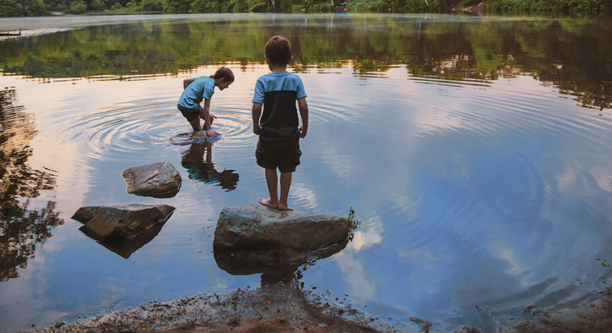 Boys standing on rocks playing in the lake