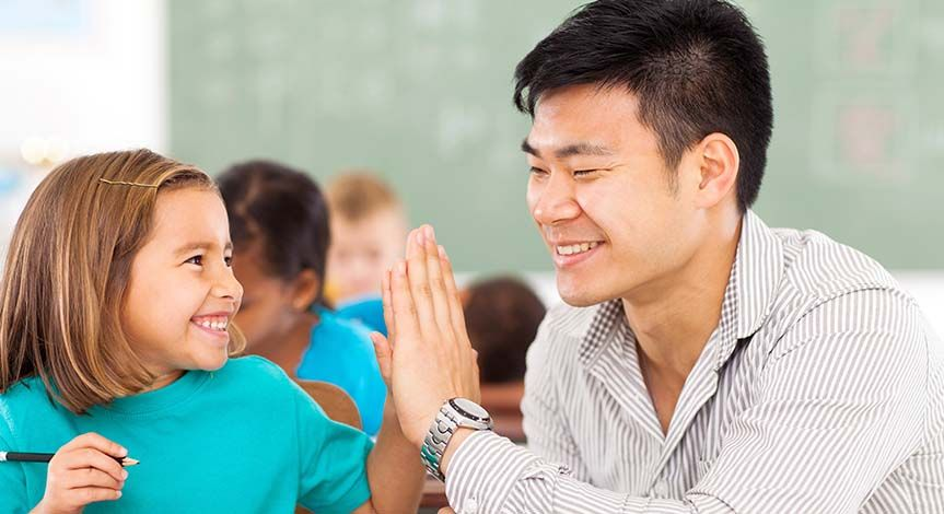 Girl high fiving teacher in the classroom while working on school work
