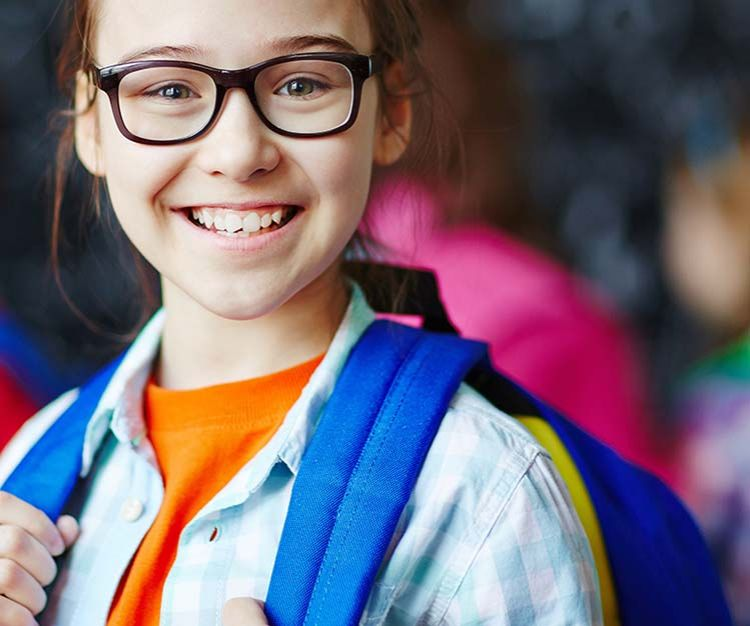 Girl wearing a school bag and black glasses smiling
